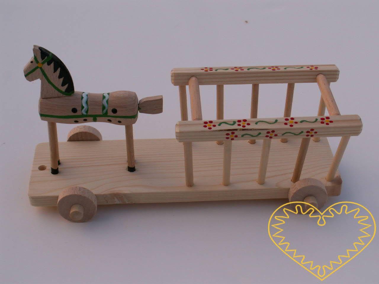 Dřevěný vozík s koníkem v přírodní barvě. Krásně malovaný suvenýr vycházející ze vzorů tradičních dětských dřevěných hraček. Koník je na společném podstavci s vozíkem a jezdí pomocí 4 koleček.