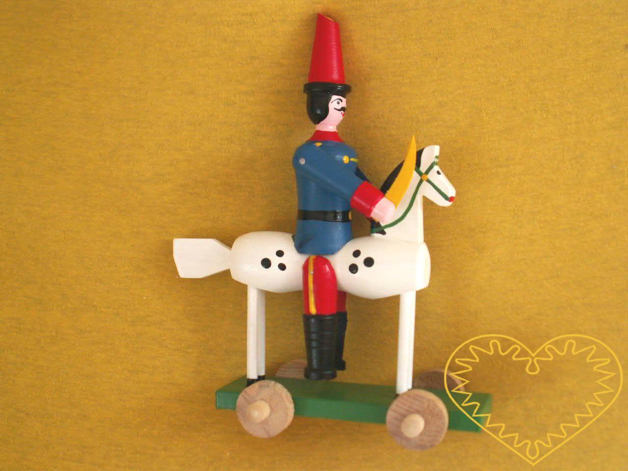 Dřevěný malovaný husar na koni. Krásně malovaný suvenýr vycházející ze vzorů tradičních dětských dřevěných hraček. Koník s husarem se pohybuje pomocí 4 koleček umístěných na podstavci.