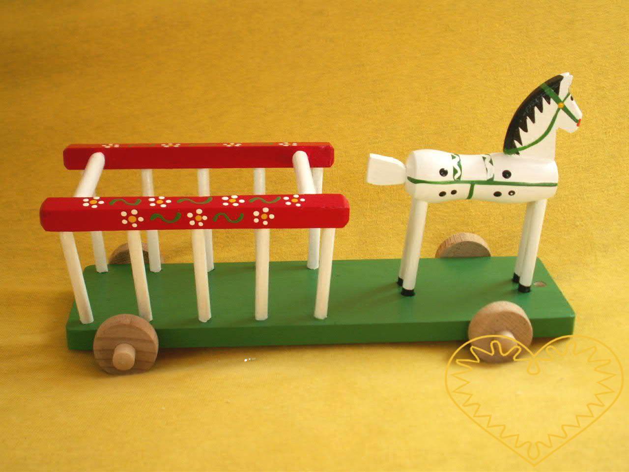 Dřevěný vozík s koníkem. Krásně malovaný suvenýr vycházející ze vzorů tradičních dětských dřevěných hraček. Koník je na společném podstavci s vozíkem a jezdí pomocí 4 koleček.