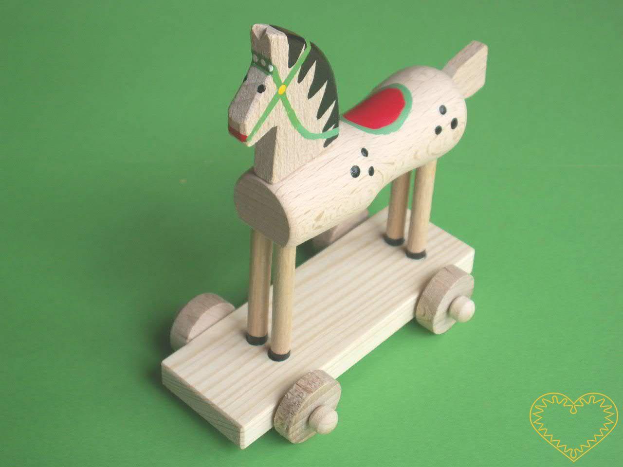 Dřevěný koník na kolečkách - větší. Krásně malovaný suvenýr vycházející ze vzorů tradičních dětských dřevěných hraček. Koník na podstavci se pohybuje pomocí 4 koleček.