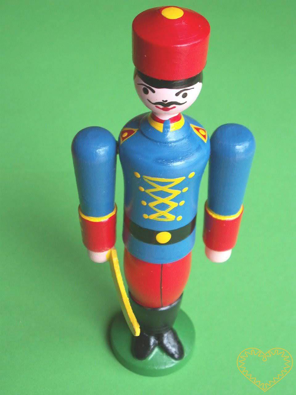 Malovaný dřevěný husar. Krásně malovaný suvenýr vycházející ze vzorů tradičních dětských dřevěných hraček. Soustružená figurka husara ve vojenské uniformě má pohyblivé ruce ve směru nahoru - dolu. V pravé ruce drží šavli.
