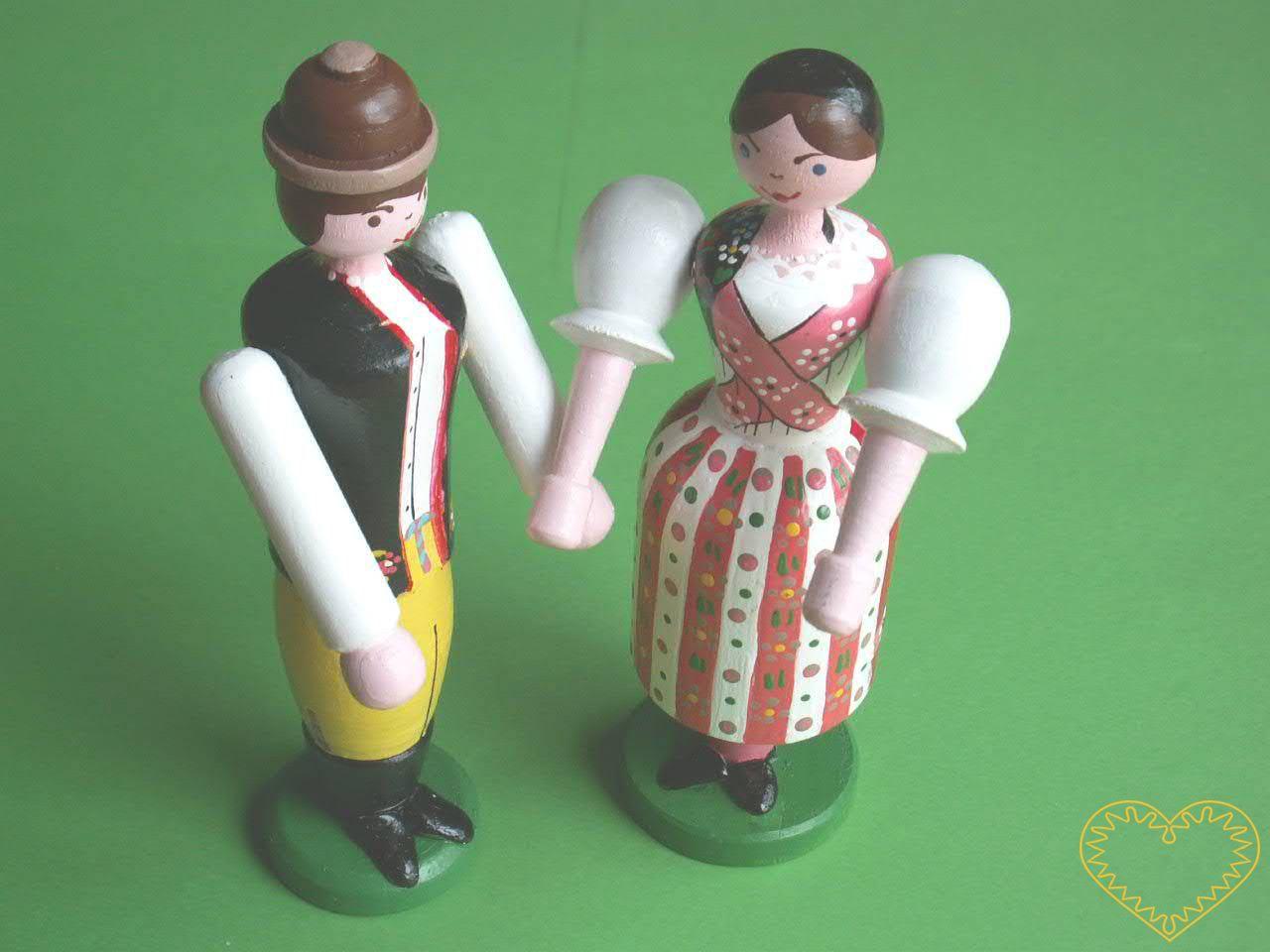 Panenka a panáček v chodském kroji. Krásně malovaný suvenýr vycházející ze vzorů tradičních dětských dřevěných hraček. Soustružené figurky představují ženu a muže v chodském kroji. Obě postavičky mají pohyblivé ruce ve směru nahoru - dolu.