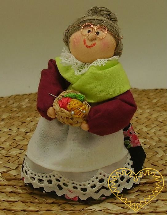Bába ss pletením - textilní figurka v prácheňském lidovém kroji, vysoká cca 10 cm. Malebný suvenýr čerpající z tradiční lidové kultury.