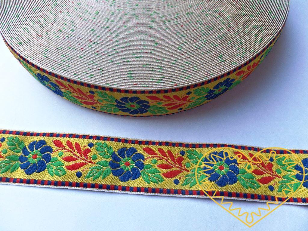Žlutá krojová stuha se vzorem - vzorovka - šíře 2,5 cm. Textilní tkaná stuha s modrými květy a červenými a zelenými lístky se uplatní zvláště při výrobě krojů a předmětů tradiční lidové kultury. Vhodná též k lemování tkanin a šatů panenek a maňásků.