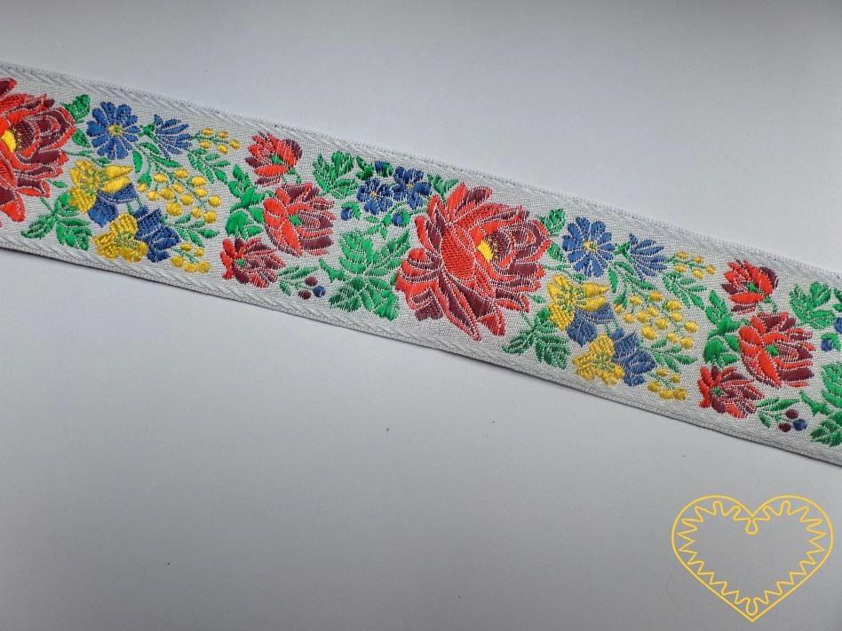 Široká bílá krojová stuha s bohatým květinovým vzorem - vzorovka š 5 cm. Textilní tkaná stuha je vhodná zvláště k lemování tkanin, zdobení krojů a šatů panenek a maňásků.