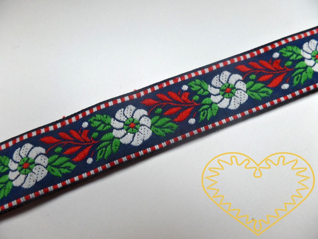 Modrá krojová stuha se vzorem - vzorovka - šíře 2,5 cm. Textilní tkaná stuha s modrými květy a červenými a zelenými lístky se uplatní zvláště při výrobě krojů a předmětů tradiční lidové kultury. Vhodná též k lemování tkanin a šatů panenek a maňásků.