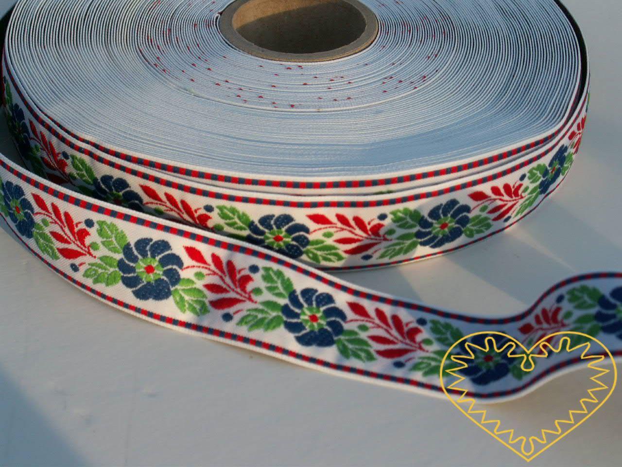 Bílá krojová stuha se vzorem - vzorovka - šíře 2,5 cm. Textilní tkaná stuha s modrými květy a červenými a zelenými lístky se uplatní zvláště při výrobě krojů a předmětů tradiční lidové kultury. Vhodná též k lemování tkanin a šatů panenek a maňásků.