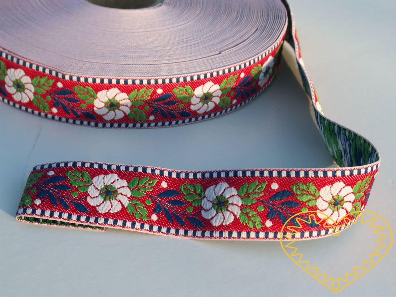 Červená krojová stuha se vzorem - vzorovka - šíře 2,5 cm. Textilní tkaná stuha s bílými květy a modrými a zelenými lístky se uplatní zvláště při výrobě krojů a předmětů tradiční lidové kultury. Vhodná též k lemování tkanin a šatů panenek a maňásků.