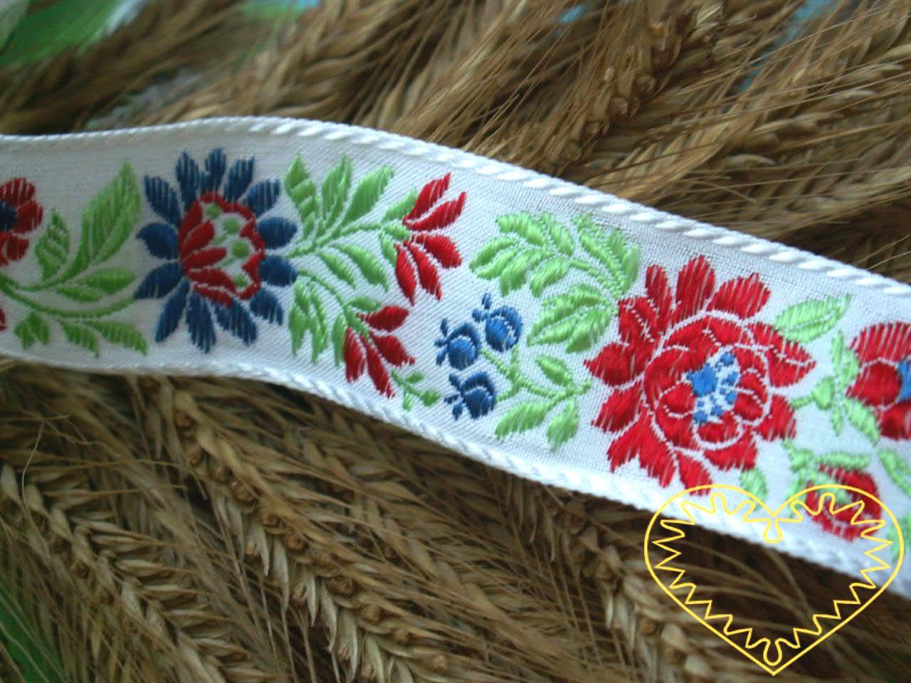 Bílá krojová stuha s červeným květinovým vzorem - vzorovka š 3,5 cm. Textilní tkaná stuha se vzorem modrých a červených květů je vhodná zvláště k lemování tkanin, zdobení krojů a šatů panenek a maňásků.