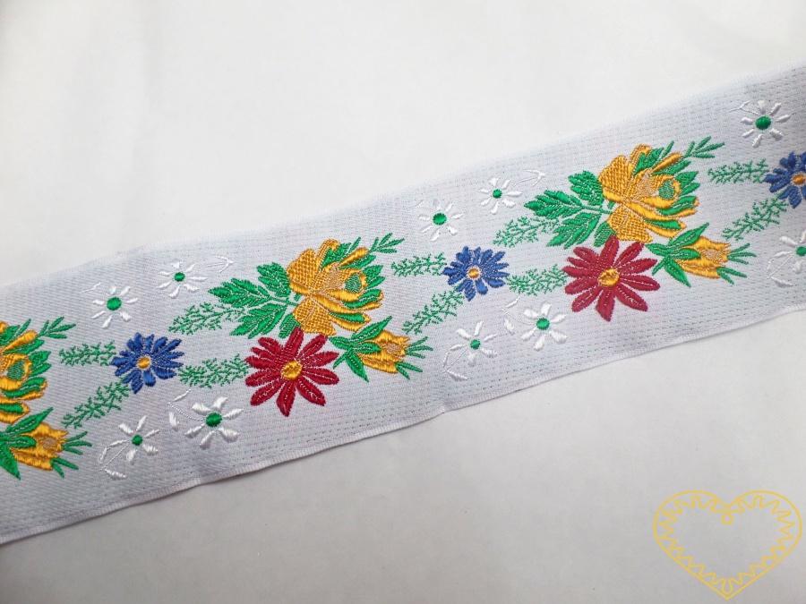 Bílá krojová stuha s barevnými květy - viskóza vzorovka š 7 cm. Textilní tkaná stuha je vhodná zvláště k lemování tkanin, zdobení krojů a šatů panenek a maňásků.
