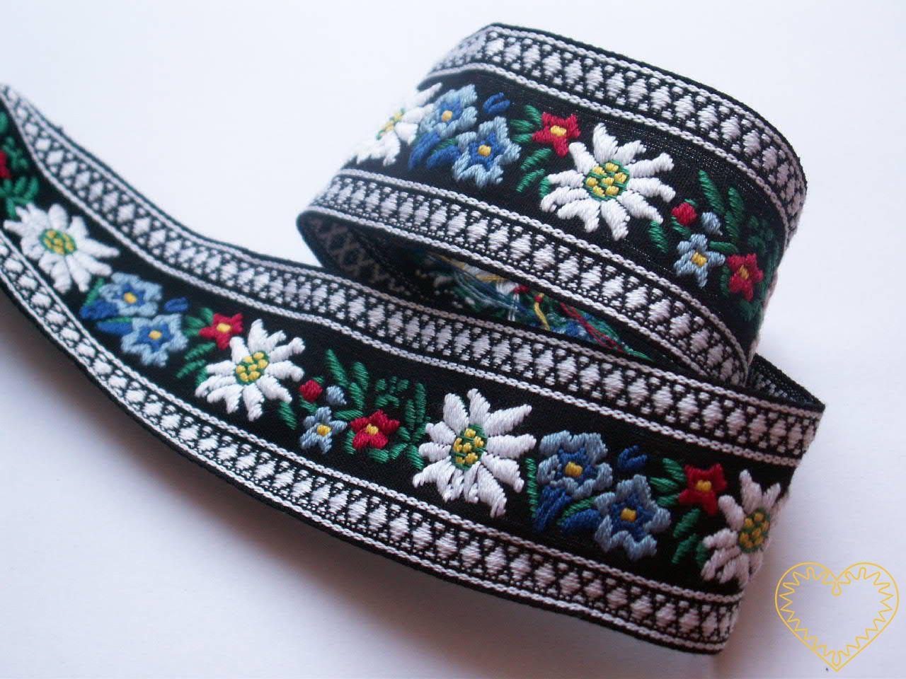 Černá krojová stuha s alpskými květy - vzorovka - šíře 4,5 cm. Textilní tkaná stuha s jemným vzorkem je vhodná zvláště k lemování tkanin, zdobení krojů a šatů panenek a maňásků. Vzory s alpskými květy jsou obzvláště oblíbeny v lidovém oděvu u našich