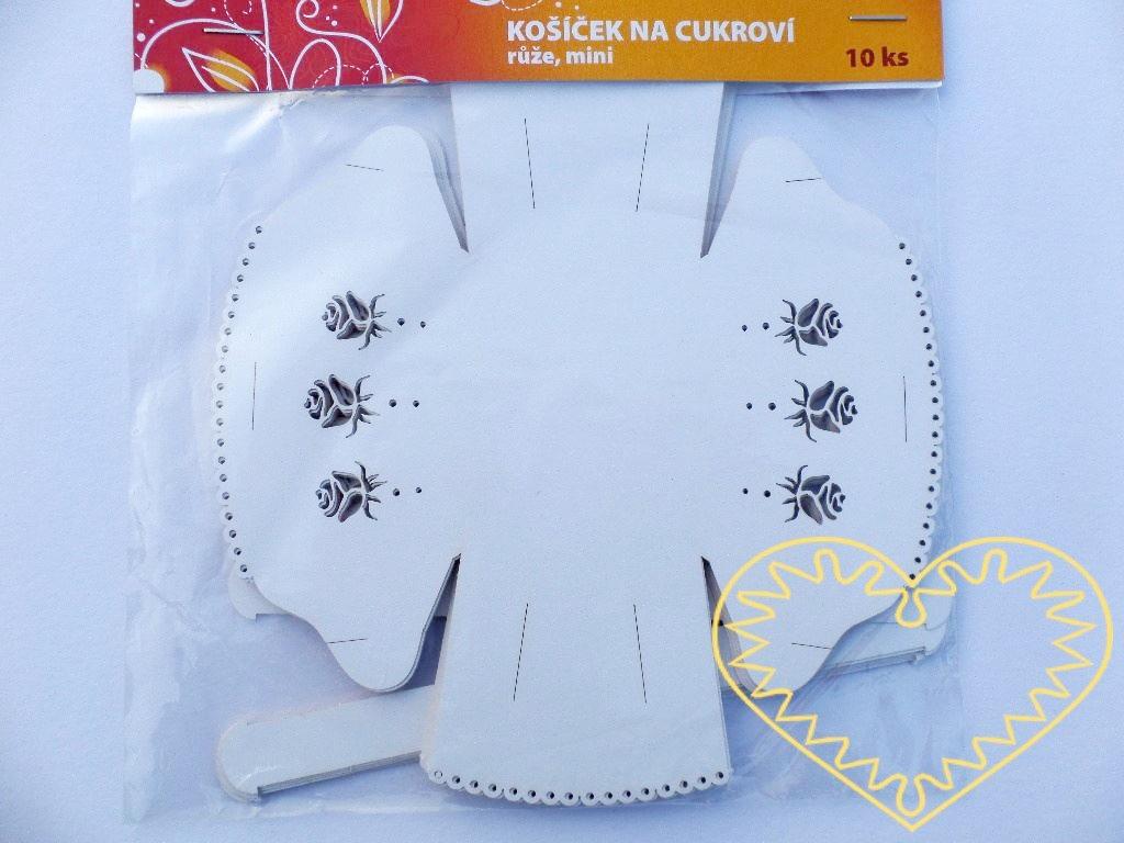 Malé bílé papírové košíčky na cukroví s ouškem - 10 ks. Jedná se o papírový výřez. Košíček má boky zdobeny vyříznutými jemnými růžičkami. Okraje navíc dotváří obloučky s drobnými kulatými otvory. Košíčky jsou v balení v rozloženém stavu s naznačenými