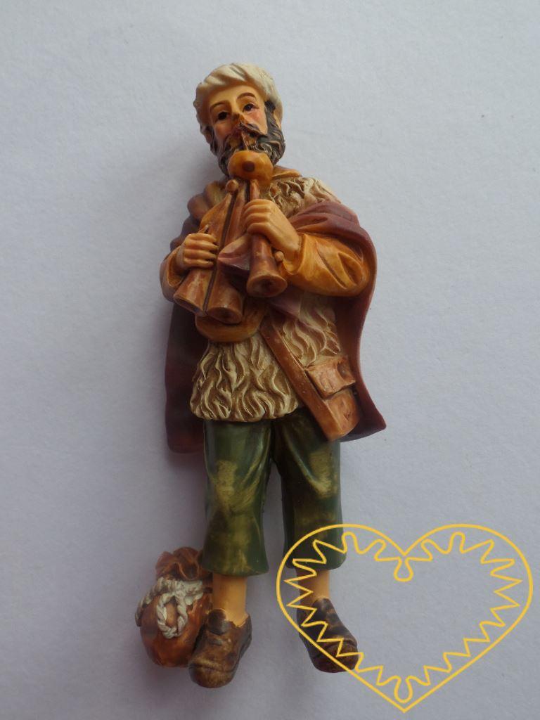 Vousatý dudák v čepici, oděvu ze srsti, hnědém plášti a krátkých kalhotách s dechovými trojhlasými dudami - figurka. U nohy dudáka leží sáček. Vhodná postava do betlémů i jako samostatná dekorace.